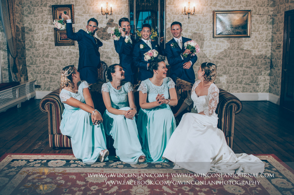 creative and fun portrait of the bride, bridesmaids and the groom and his best men posing with the bouquets in the drawing room. Wedding photography at Parklands Quendon Hall by preferred supplier gavin conlan photography Ltd