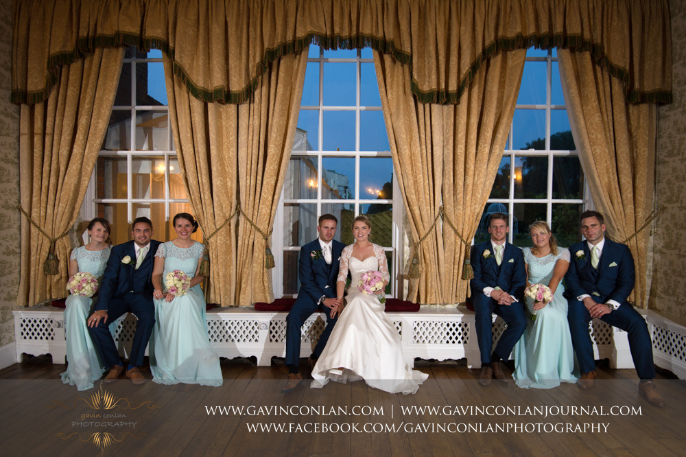 creative portrait of the bride, groom, bridesmaids and best men posing on the window seat in the drawing room. Wedding photography at Parklands Quendon Hall by preferred supplier gavin conlan photography Ltd