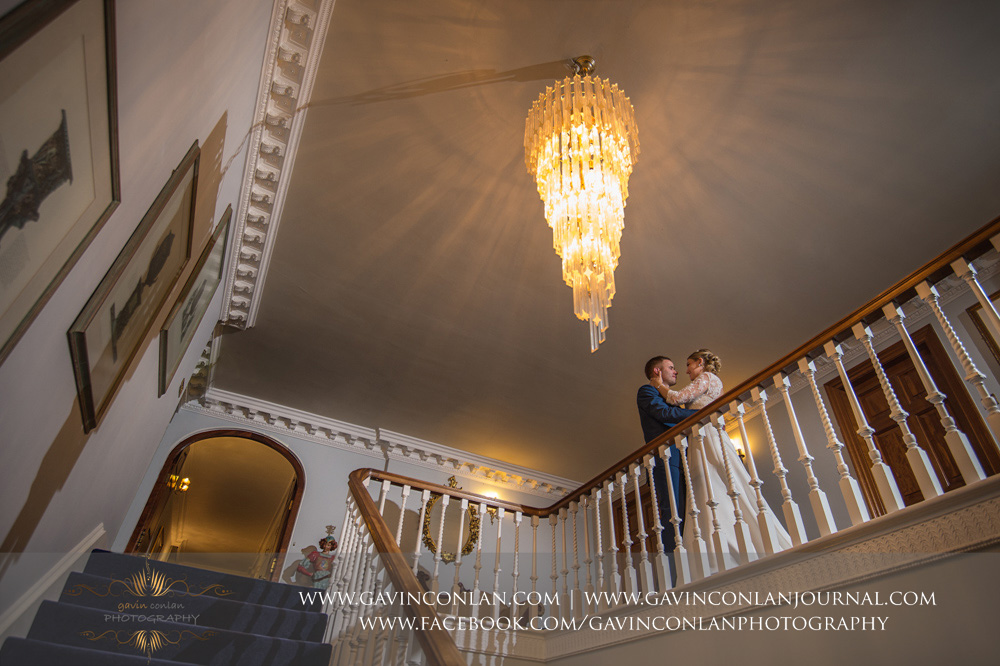 creative portrait of the bride and groom posing upstairs next to the grand staircase. Wedding photography at Parklands Quendon Hall by preferred supplier gavin conlan photography Ltd