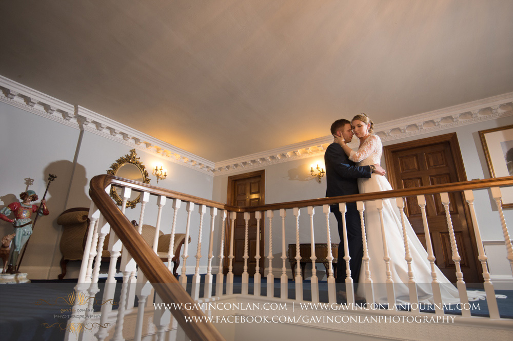 creative portrait of the bride and groom posing upstairs next to the grand staircase - a beautiful moment created. Wedding photography at  Parklands Quendon Hall  by preferred supplier  gavin conlan photography Ltd
