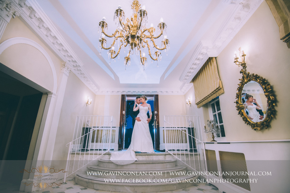 creative portrait of the bride and groom posing in the entrance area Parklands - a beautiful moment. Wedding photography at Parklands Quendon Hall by by preferred supplier gavin conlan photography Ltd