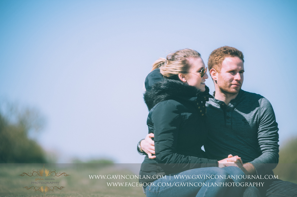 creative portrait of Victoria and James sitting down looking out to the Solent at  Old Harry Rocks , Engagement Session in Bournemouth, Dorset by  gavin conlan photography Ltd