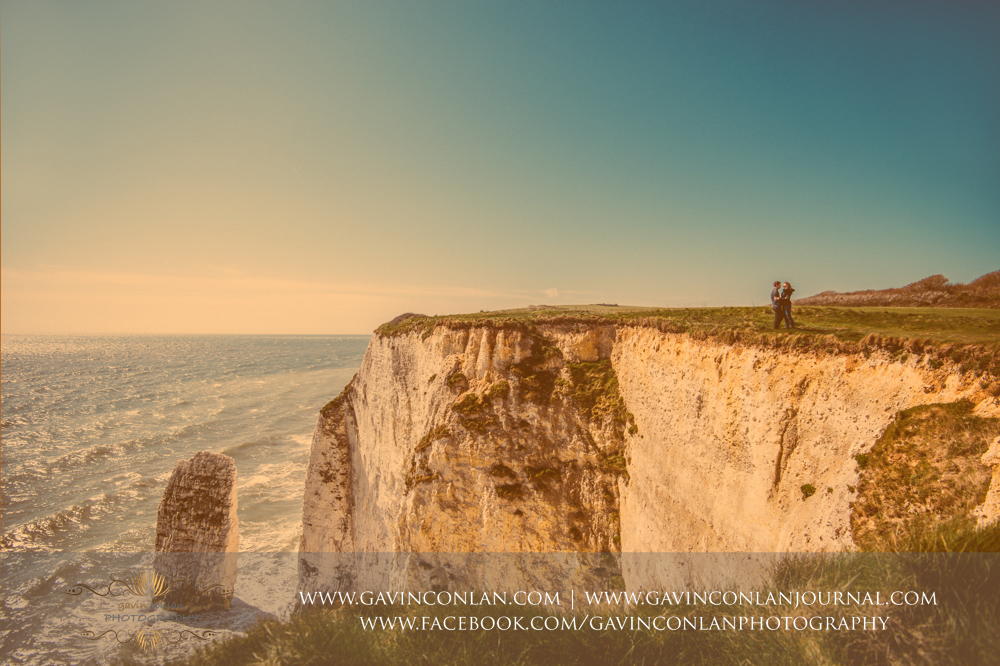 creative fine art portrait of Victoria and James cuddling next to the cliffs edge at  Old Harry Rocks . Engagement Session in Bournemouth, Dorset by  gavin conlan photography Ltd