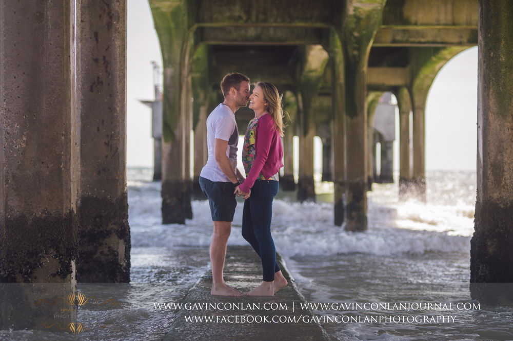 creative portrait of Victoria and James on the beach underneath Boscombe Pier. Engagement Session in Bournemouth, Dorset by  gavin conlan photography Ltd