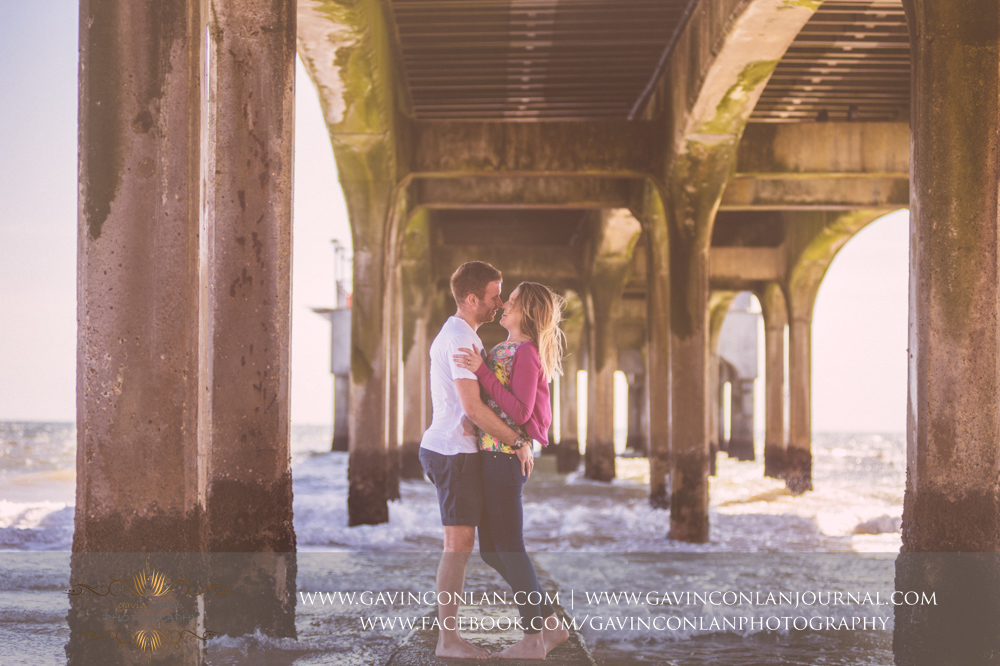 creative portrait of Victoria and James underneath  Boscombe Pier . Engagement Session in Bournemouth, Dorset by  gavin conlan photography Ltd