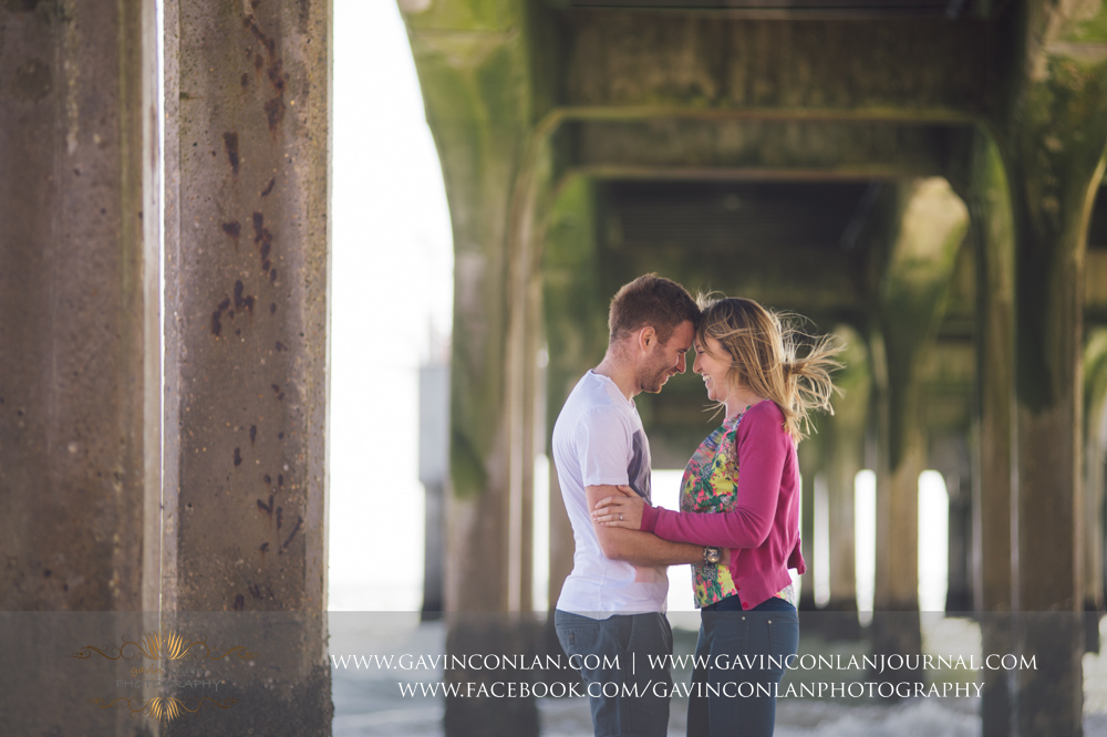 absolute happiness in this portrait of Victoria and James underneath  Boscombe Pier . Engagement Session in Bournemouth, Dorset by  gavin conlan photography Ltd