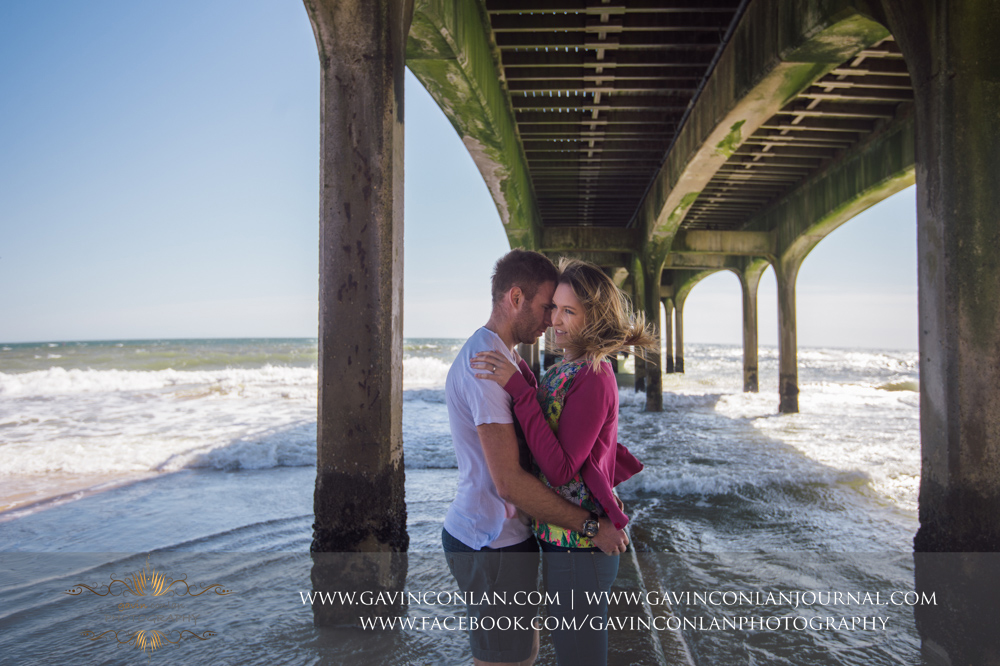 creative fashion portrait of Victoria and James underneath  Boscombe Pier . Engagement Session in Bournemouth, Dorset by  gavin conlan photography Ltd
