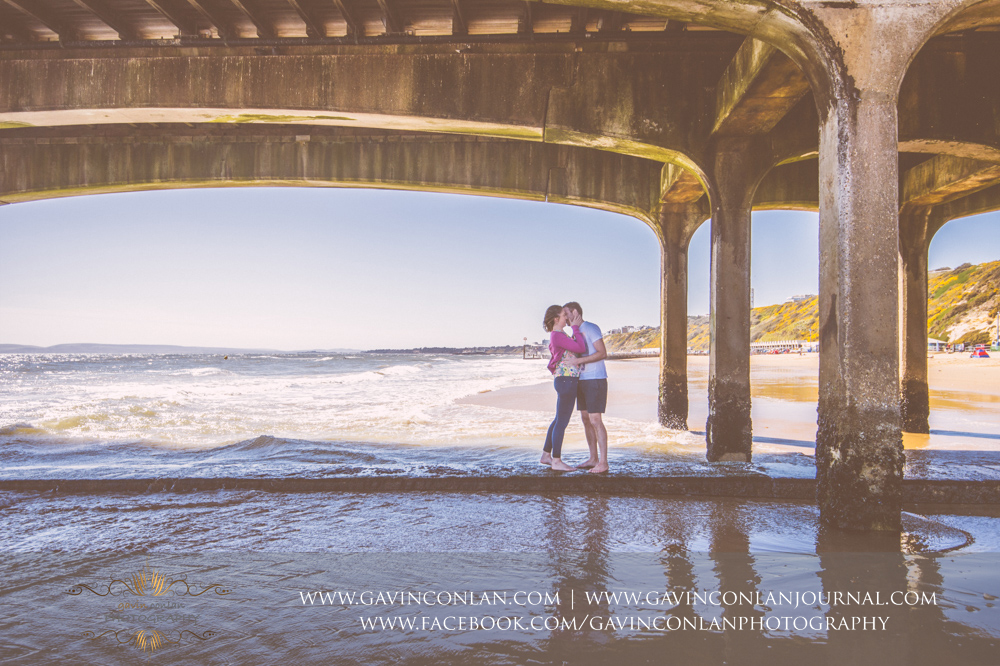 creative fine art portrait of Victoria and James together underneath  Boscombe Pier . Engagement Session in Bournemouth, Dorset by  gavin conlan photography Ltd