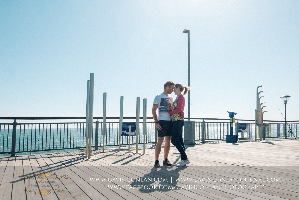 creative full length portrait of Victoria and James on  Boscombe Pier . Engagement Session in Bournemouth, Dorset by  gavin conlan photography Ltd