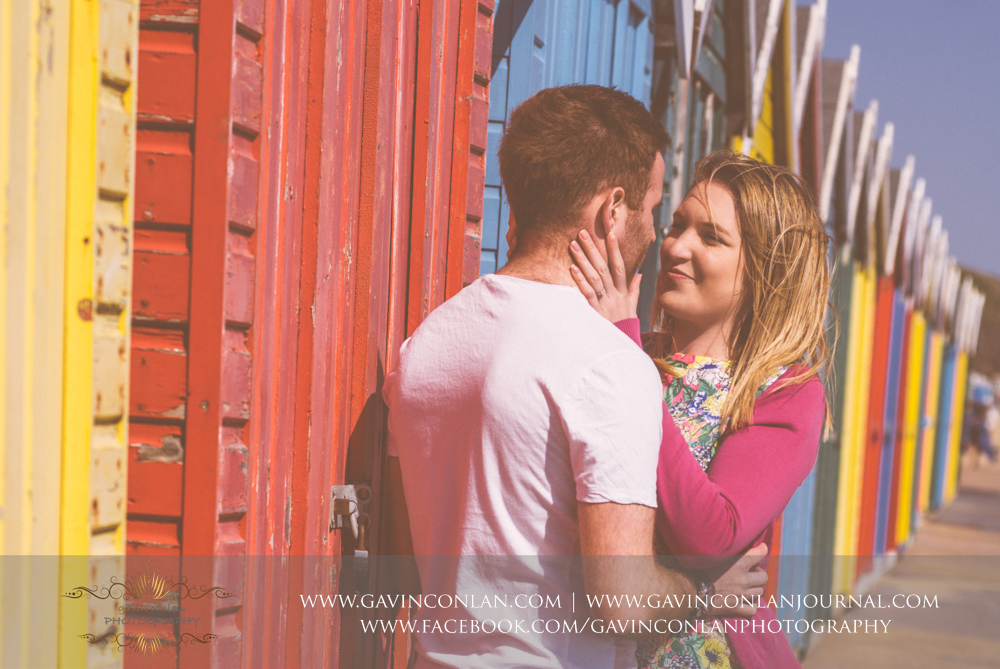 creative fine art portrait of Victoria and James cuddling in front of the multi colour beach huts next to  Boscombe Pier . Engagement Session in Bournemouth, Dorset by  gavin conlan photography Ltd