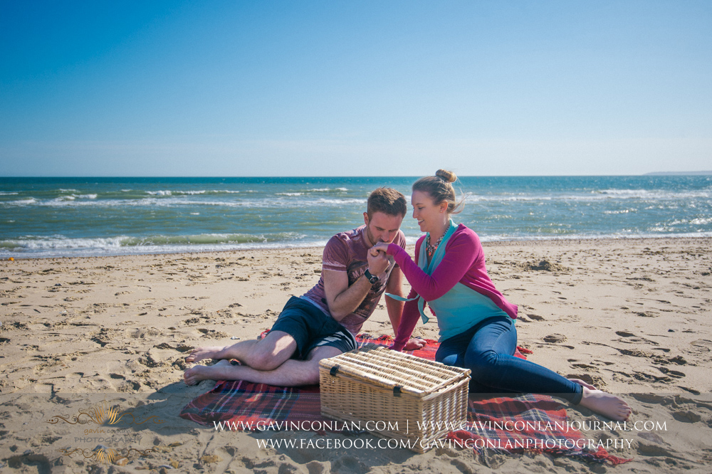 portrait of James kissing Victoria's hand whilst sitting on the beach near  Boscombe Pier . Engagement Session in Bournemouth, Dorset by  gavin conlan photography Ltd
