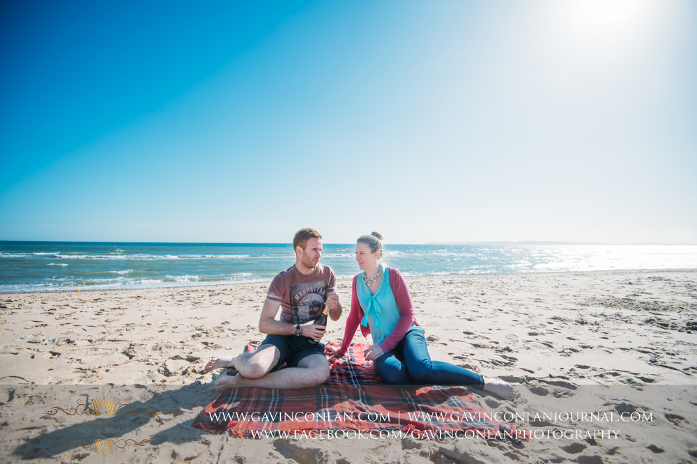 creative portrait of Victoria and James sitting on the beach near  Boscombe Pier  having fun. Engagement Session in Bournemouth, Dorset by  gavin conlan photography Ltd