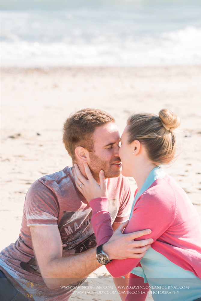 portrait of Victoria and James sitting on the beach near  Boscombe Pier  about to share a kiss. Engagement Session in Bournemouth, Dorset by  gavin conlan photography Ltd