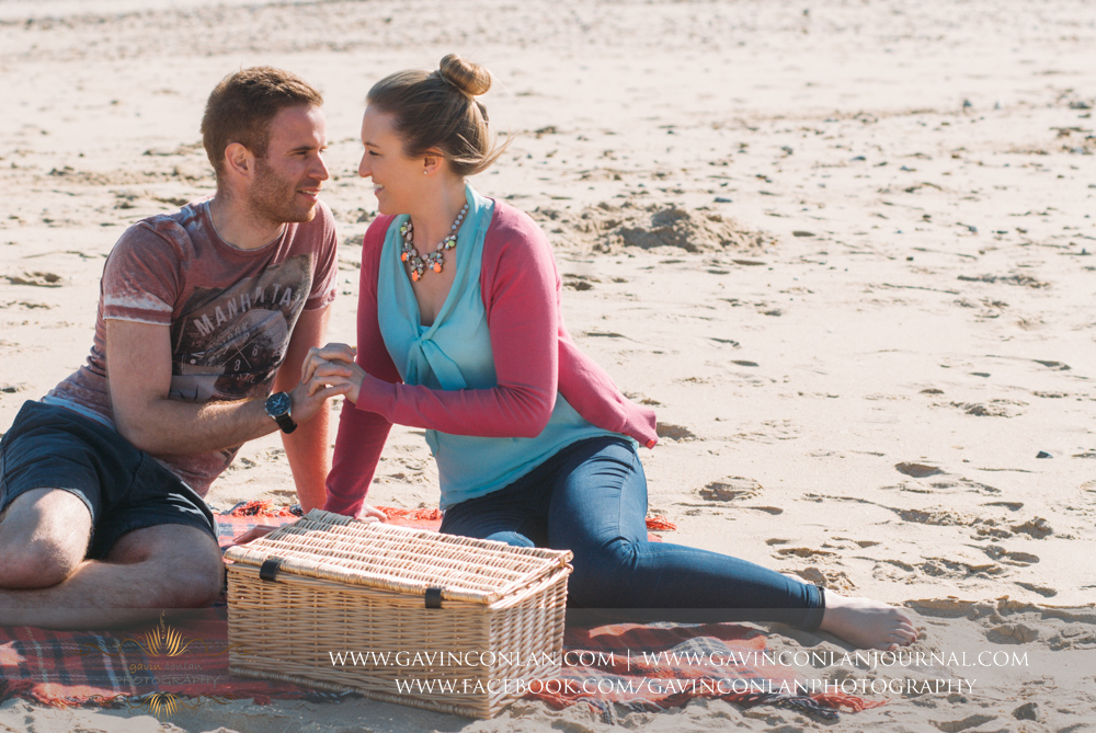 portrait of Victoria and James holding hands sitting on the beach near  Boscombe Pier . Engagement Session in Bournemouth, Dorset by  gavin conlan photography Ltd