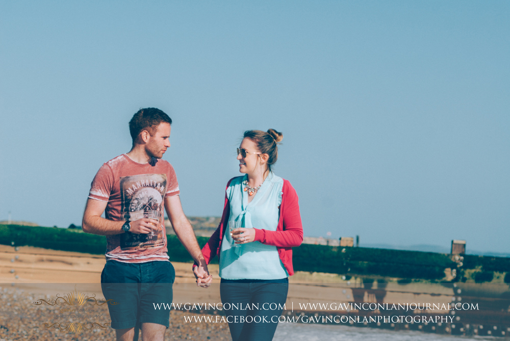 creative portrait of Victoria and James walking along the beach near  Boscombe Pier  holding hands. Engagement Session in Bournemouth, Dorset by  gavin conlan photography Ltd