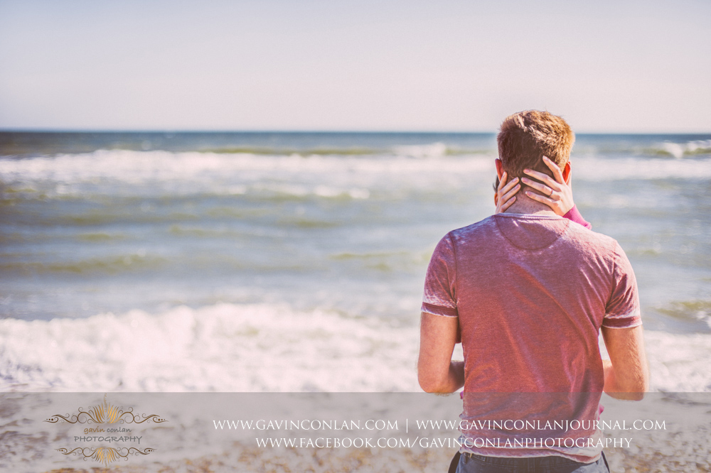 creative portrait showcasing Victoria's hand around the back of James's head on the beach near  Boscombe Pier . Engagement Session in Bournemouth, Dorset by  gavin conlan photography Ltd