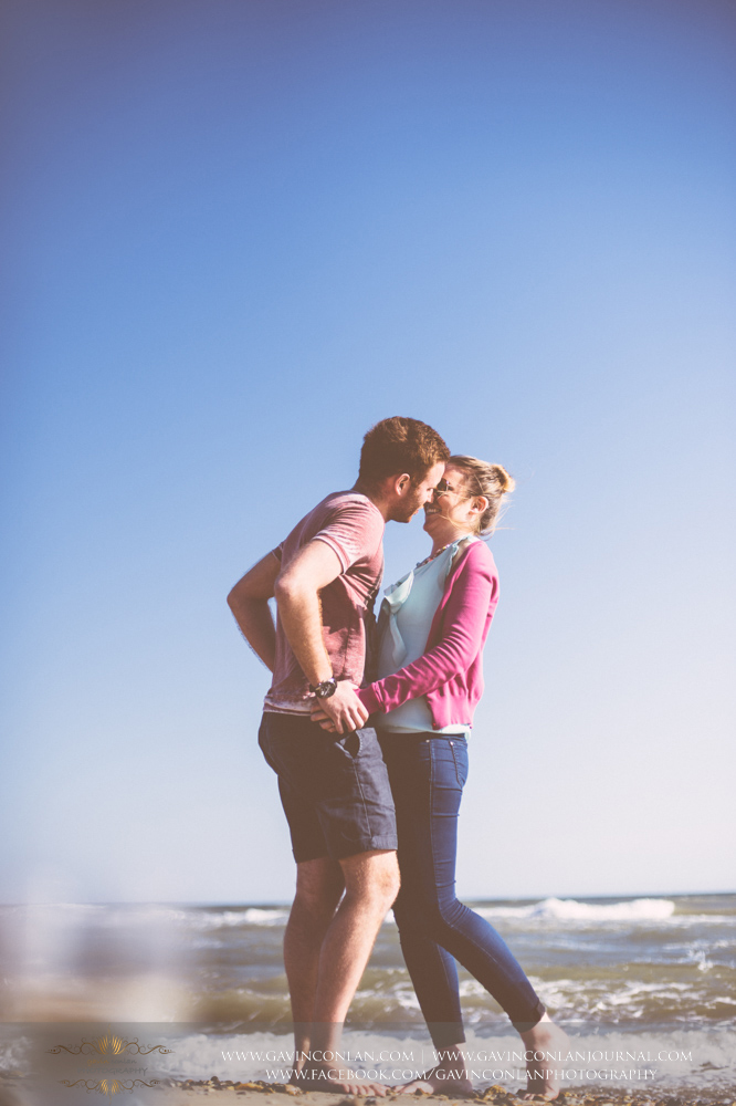 full length portrait of Victoria and James on the beach near  Boscombe Pier . Engagement Session in Bournemouth, Dorset by  gavin conlan photography Ltd