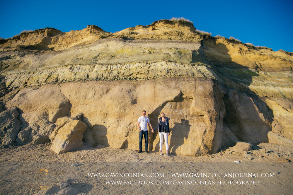 portrait of Victoria and James standing in front of The layers of sands, gravels and clays that make up  Hengistbury Head  which were formed around 65 million years ago. Engagement Session in Bournemouth, Dorset by  gavin conlan photography Ltd