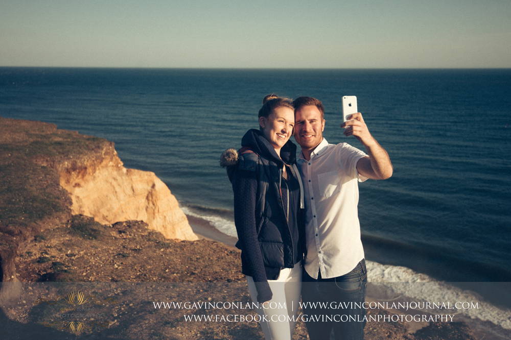 Victoria and James taking a selfie at  Hengistbury Head .  Engagement Session in Bournemouth, Dorset by  gavin conlan photography Ltd