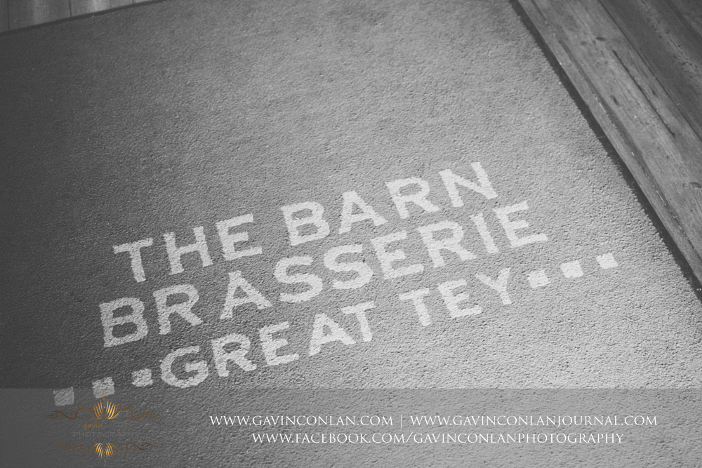 creative black and white photograph showcasing The Barn Brasserie Great Tey written on the door matt. Wedding photography at The Barn Brasserie by Essex wedding photographer gavin conlan photography Ltd