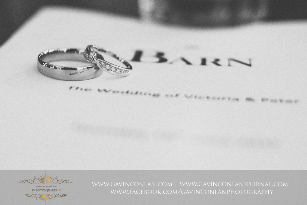 creative black and white photograph of the wedding rings with the Barn and The wedding of Victoria and Peter written on the background. Wedding photography at  The Barn Brasserie  by Essex wedding photographer  gavin conlan photography Ltd