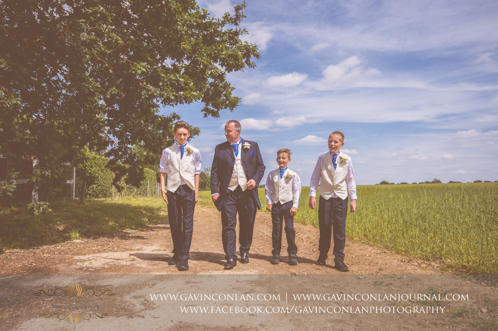 creative portrait of the groom walking with his sons in the field next to The Barn. Wedding photography at The Barn Brasserie by Essex wedding photographer gavin conlan photography Ltd