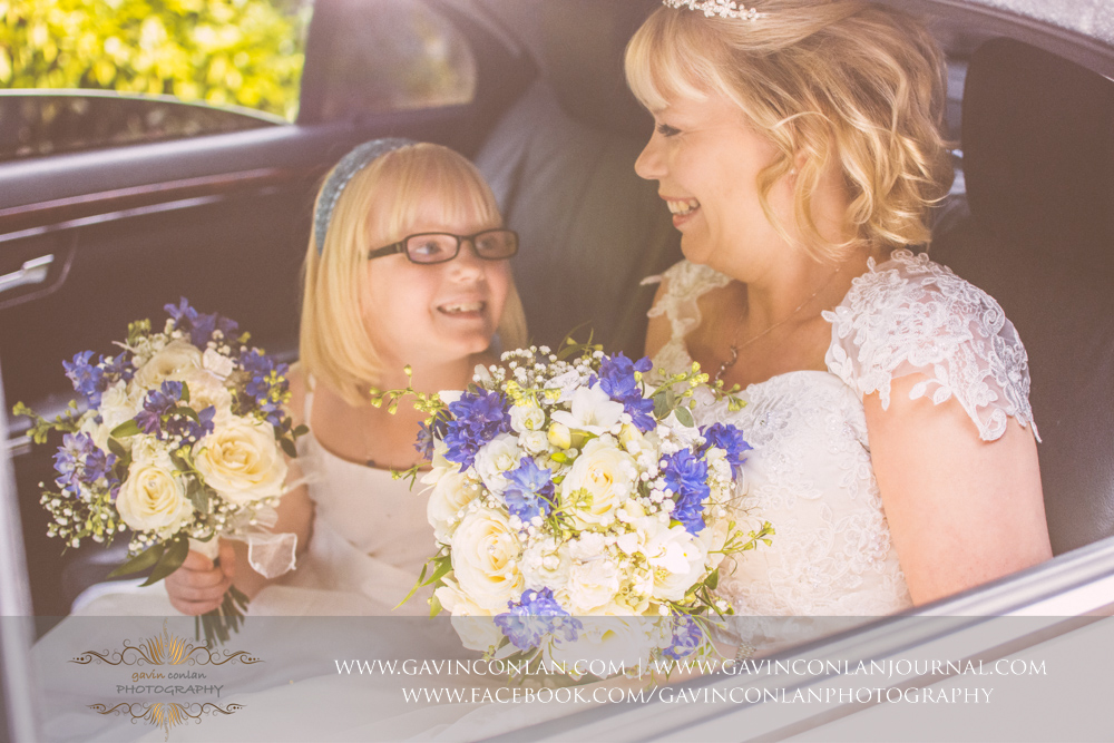 beautiful portrait of the gorgeous bride and her lovely daughter looking at each other smiling in the back of the wedding car. Wedding photography at The Barn Brasserie by Essex wedding photographer gavin conlan photography Ltd