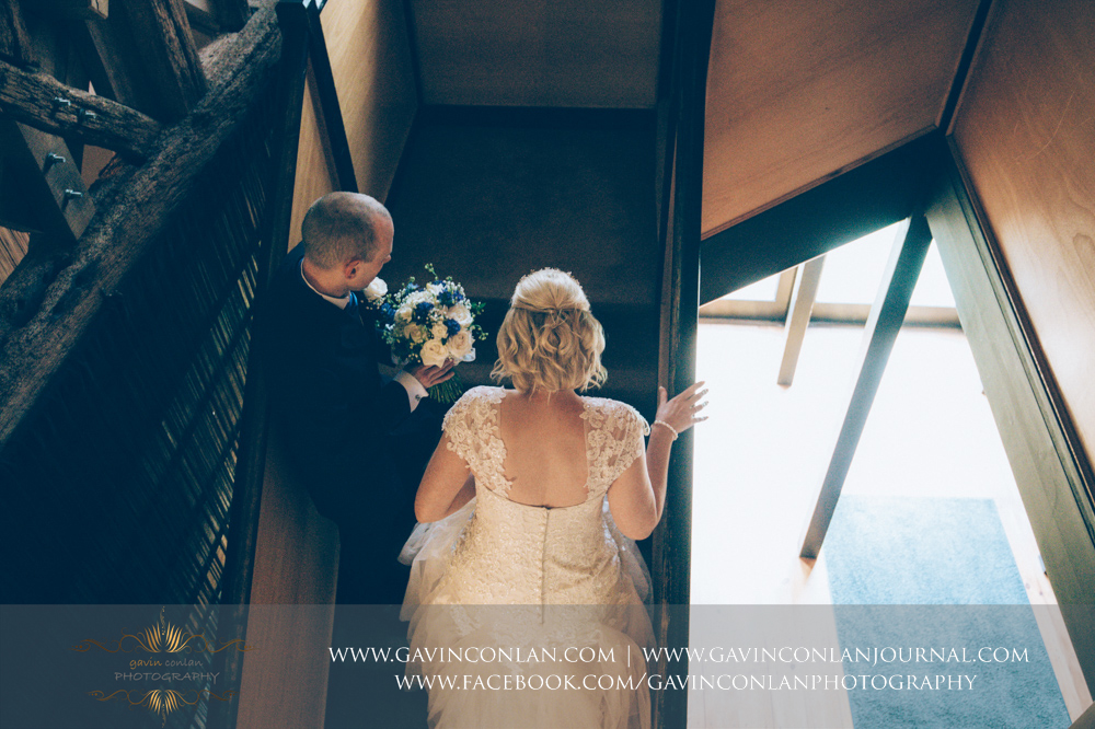 creative portrait of the bride and her brother walking up the stairs to the wedding ceremony. Wedding photography at  The Barn Brasserie  by Essex wedding photographer  gavin conlan photography Ltd