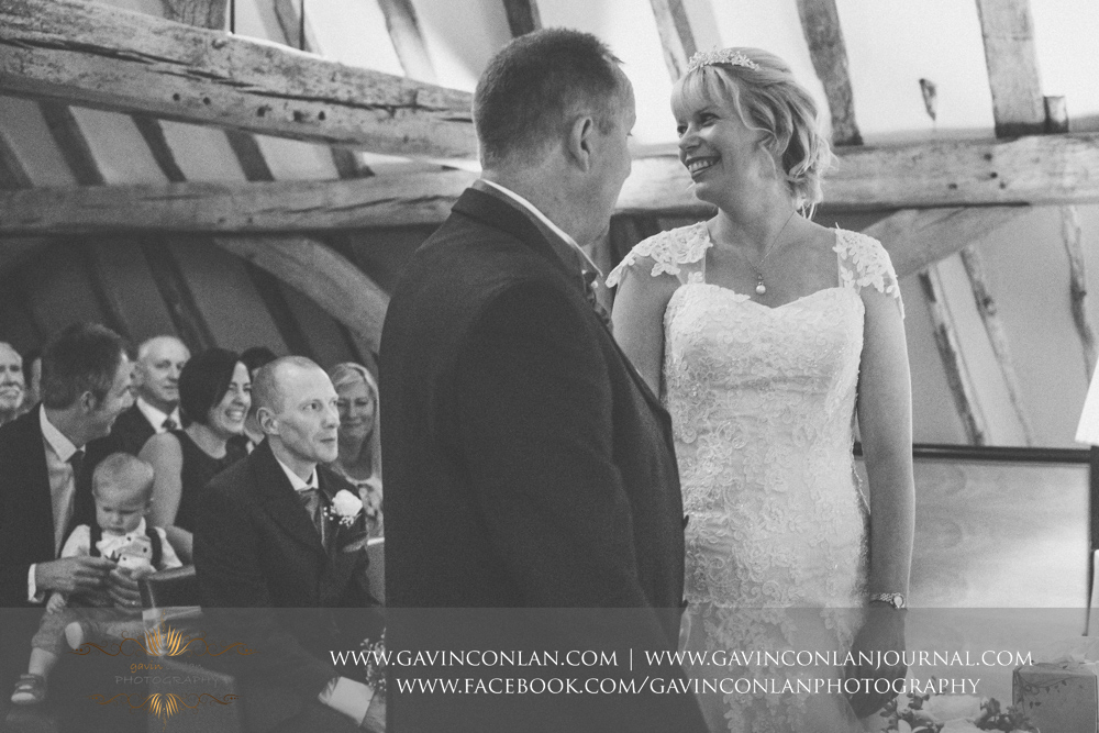 beautiful black and white ceremony photograph of the bride looking back at her guests smiling. Wedding photography at The Barn Brasserie by Essex wedding photographer gavin conlan photography Ltd