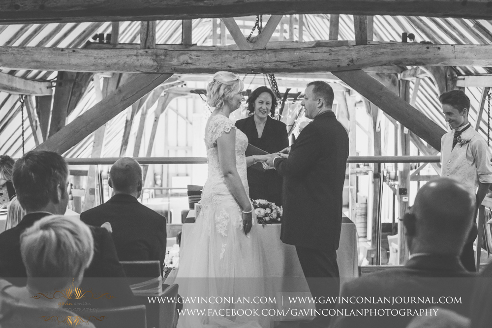 creative black and white ceremony photograph showing the groom putting the wedding ring on his brides finger during the service. Wedding photography at The Barn Brasserie by Essex wedding photographer gavin conlan photography Ltd