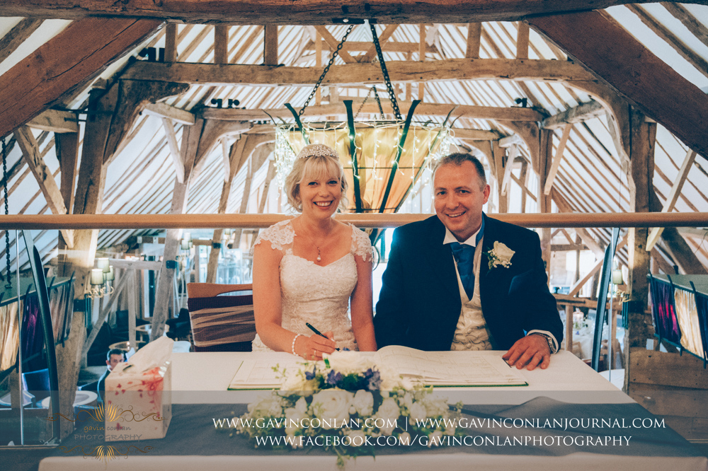 portrait of the bride and groom signing the register after their wedding ceremony. Wedding photography at  The Barn Brasserie  by Essex wedding photographer  gavin conlan photography Ltd
