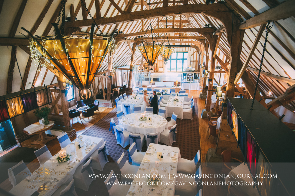 creative portrait of the bride and groom holding hands inside The Barn showcasing the room set up for their wedding breakfast. Wedding photography at The Barn Brasserie by Essex wedding photographer gavin conlan photography Ltd