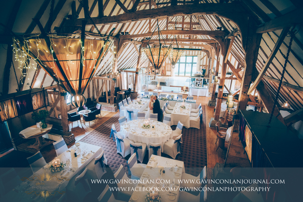 creative portrait of the bride and groom holding hands and sharing a kiss inside The Barn showcasing the room set up for their wedding breakfast. Wedding photography at The Barn Brasserie by Essex wedding photographer gavin conlan photography Ltd