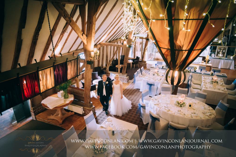creative portrait of the bride and groom holding hands walking through The Barn showcasing the room set up for their wedding breakfast. Wedding photography at The Barn Brasserie by Essex wedding photographer gavin conlan photography Ltd