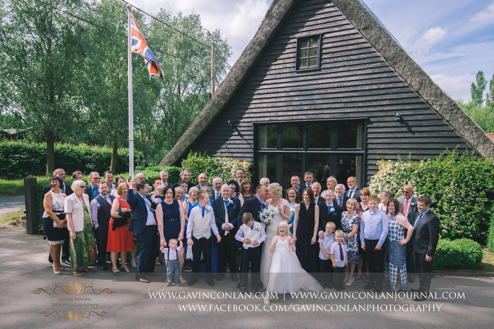 portrait of all the guests with the bride and groom outside The Barn. Wedding photography at The Barn Brasserie by Essex wedding photographer gavin conlan photography Ltd
