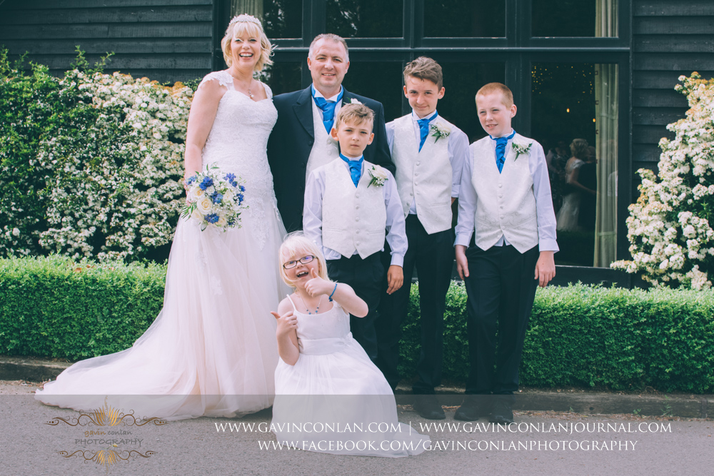 fun portrait of the bride and groom with their children outside The Barn. Wedding photography at The Barn Brasserie by Essex wedding photographer gavin conlan photography Ltd