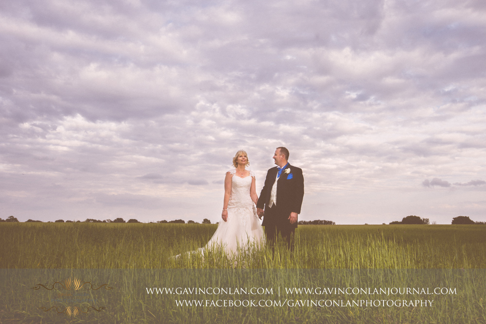 creative portrait of the groom looking at his bride in the field opposite The Barn. Wedding photography at The Barn Brasserie by Essex wedding photographer gavin conlan photography Ltd