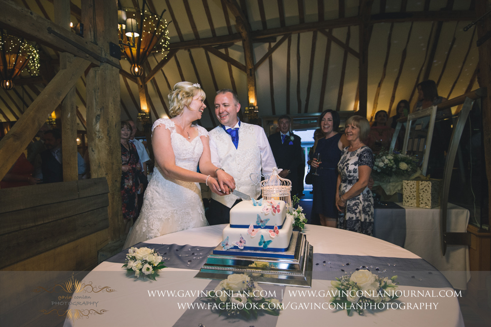 the bride and groom cutting their wedding cake. Wedding photography at  The Barn Brasserie  by Essex wedding photographer  gavin conlan photography Ltd