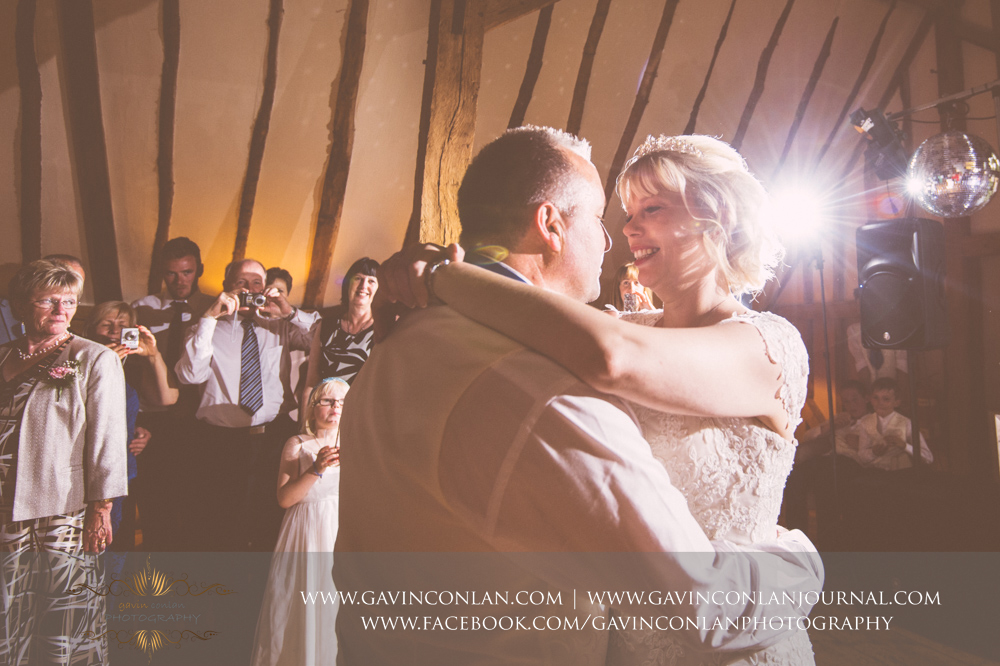 creative portrait of the bride and groom during their first dance with their guests taking photos in the background. Wedding photography at The Barn Brasserie by Essex wedding photographer gavin conlan photography Ltd