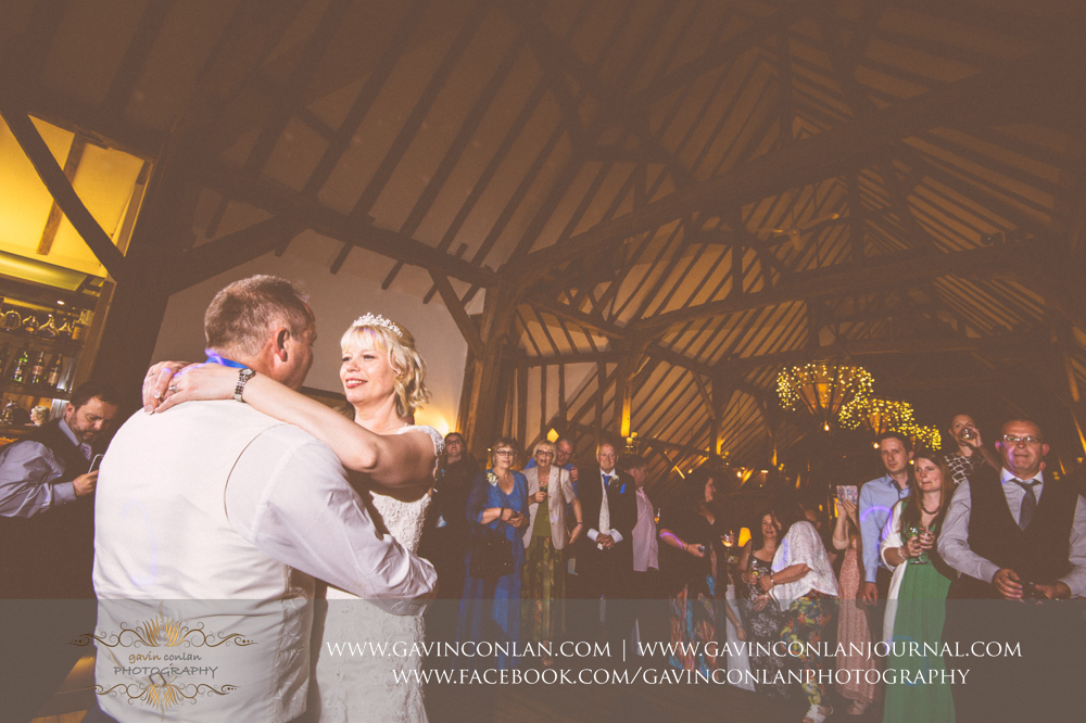 creative portrait of the bride and groom during their first dance with all their guests in the background. .Wedding photography at  The Barn Brasserie  by Essex wedding photographer  gavin conlan photography Ltd