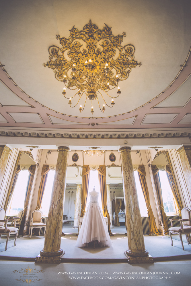 creative detail shot showcasing the brides wedding dress in The Rococco Suite. Wedding photography at  Gosfield Hall  by Essex wedding photographer  gavin conlan photography Ltd