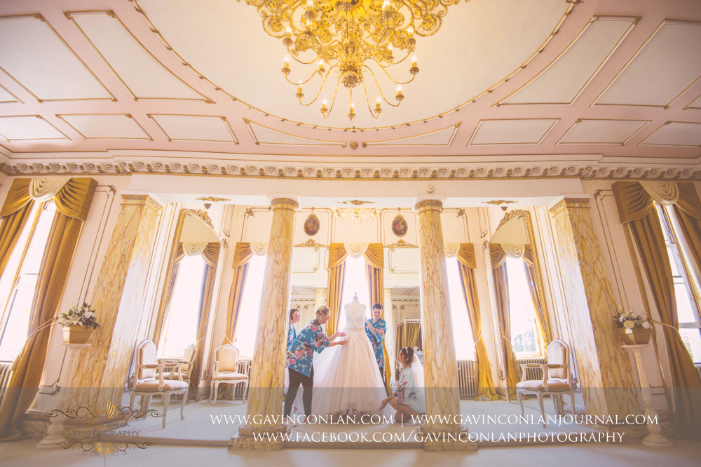 portrait of the bride and her bridesmaids looking at the brides wedding dress in The Rococco Suite. Wedding photography at  Gosfield Hall  by Essex wedding photographer  gavin conlan photography Ltd