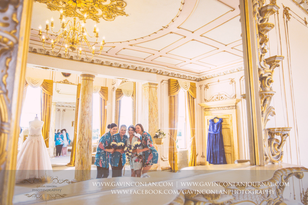 creative and fun portrait of the bride and her bridesmaids in The Rococco Suite. Wedding photography at  Gosfield Hall  by Essex wedding photographer  gavin conlan photography Ltd