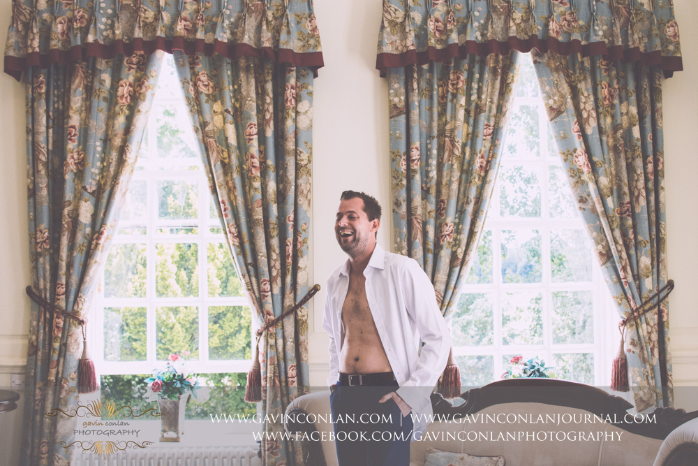 creative portrait of the groom with his shirt open laughing in The Kings Apartment. Wedding photography at  Gosfield Hall  by Essex wedding photographer  gavin conlan photography Ltd