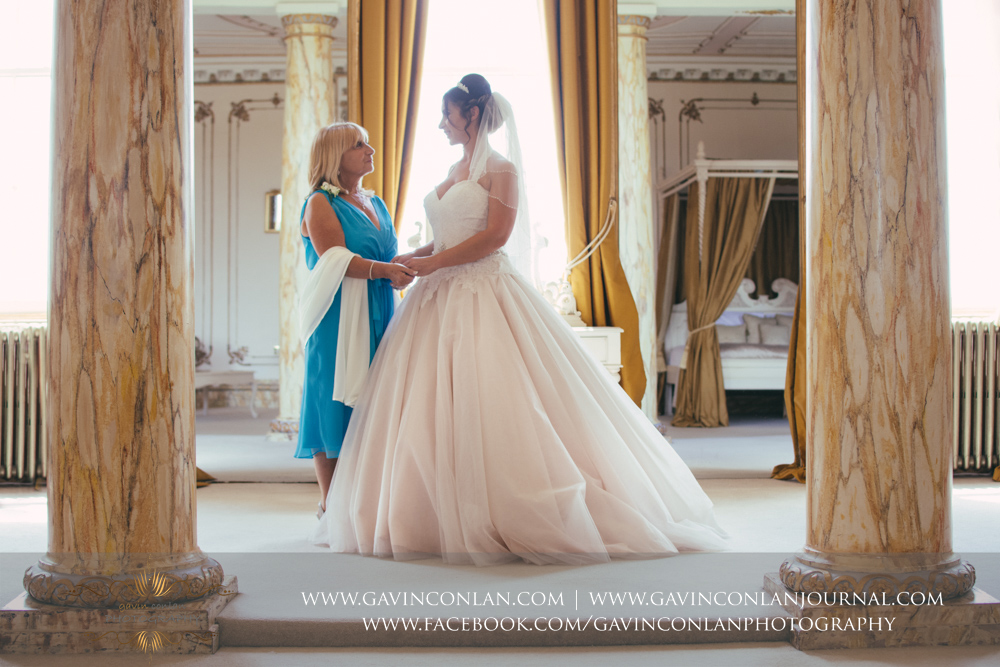 beautiful portrait of the bride and her mother holding hands in The Rococco Suite. Wedding photography at  Gosfield Hall  by Essex wedding photographer  gavin conlan photography Ltd