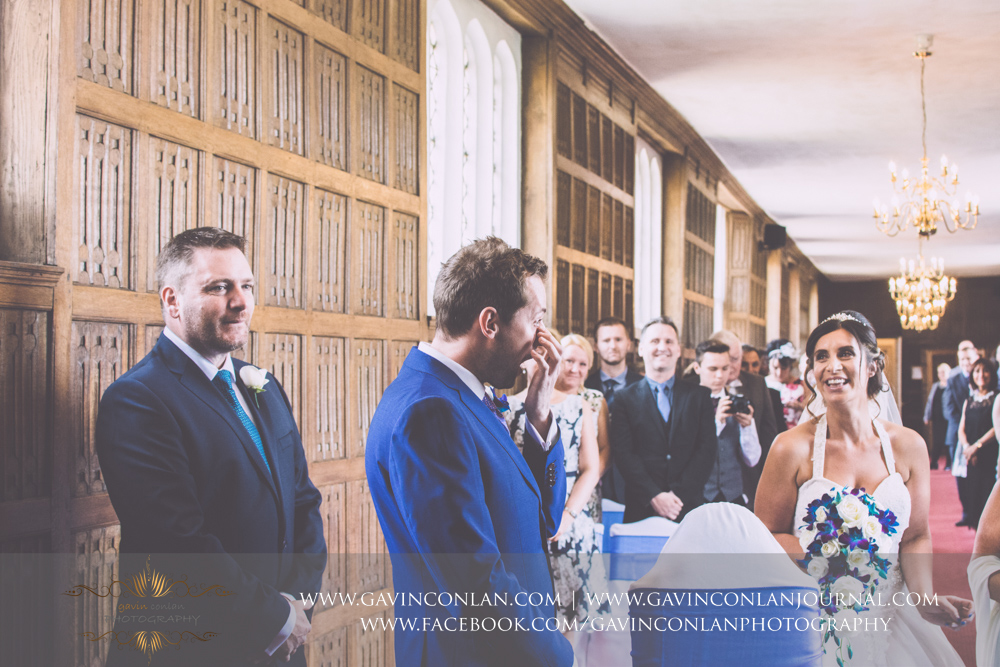a beautiful and emotive portrait as the bride and groom come together at the start of their wedding ceremony in The Queens Gallery. Wedding photography at  Gosfield Hall  by Essex wedding photographer  gavin conlan photography Ltd
