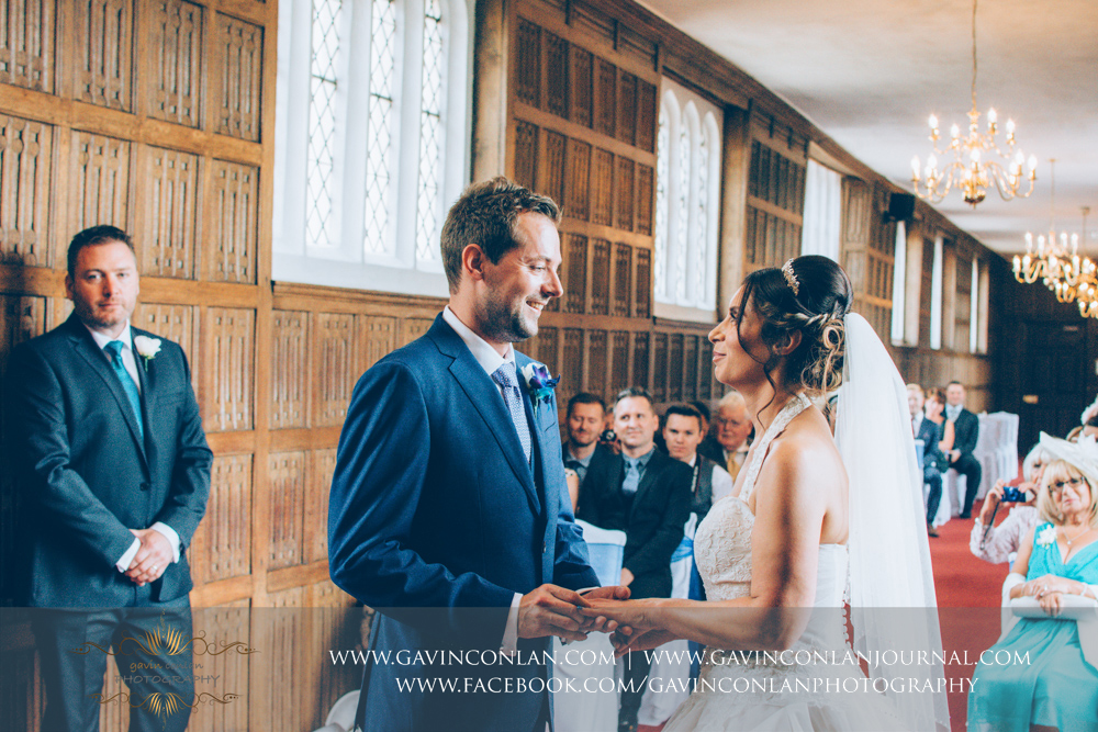 creative wedding ceremony photograph of the groom putting the ring on his brides finger in The Queens Gallery. Wedding photography at  Gosfield Hall  by Essex wedding photographer  gavin conlan photography Ltd
