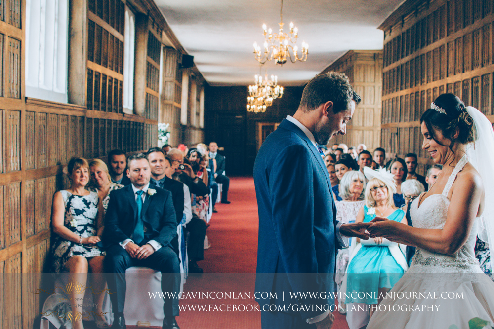 creative wedding ceremony photograph of the bride putting the ring on her grooms finger in The Queens Gallery. Wedding photography at  Gosfield Hall  by Essex wedding photographer  gavin conlan photography Ltd