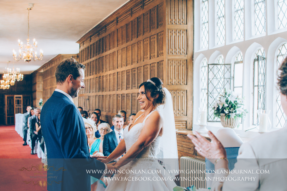 a beautiful and emotive portrait of the bride and groom holding hands during their wedding ceremony in The Queens Gallery. Wedding photography at  Gosfield Hall  by Essex wedding photographer  gavin conlan photography Ltd