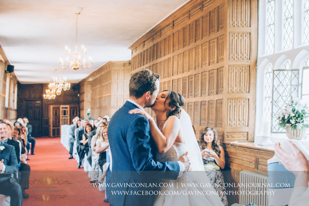 portrait of the bride and groom sharing their first kiss as Mr and Mrs in The Queens Gallery. Wedding photography at  Gosfield Hall  by Essex wedding photographer  gavin conlan photography Ltd